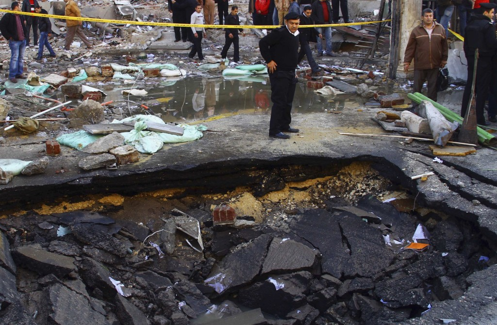THE KILL ZONE: A police officer inspects a crater made after a bomb attack in front of Cairo Security Directorate building, which includes police and state security, in downtown Cairo. PHOTO: Amr Abdallah Dalsh/REUTERS