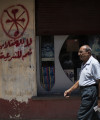 In this photograph from August 2013, an Egyptian man walks in front of a pharmacy marked with anti-Coptic and anti-coup graffiti in Assiut, Upper Egypt. Arabic graffiti reads,
